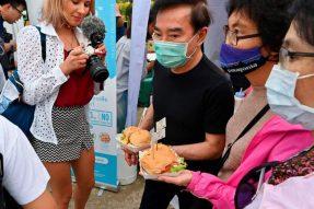 【素食新闻】2020年10月21日泰国素食节在曼谷举行,人们手捧用植物蛋白代替肉类制成的汉堡。